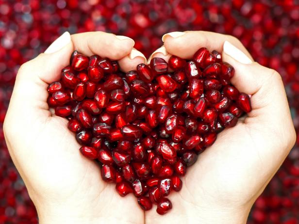 Hands holding pomegranate arils in the shape of a heart.